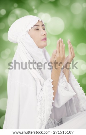 Young muslim woman praying on the GOD while wearing white clothes, shot with bokeh background - stock photo