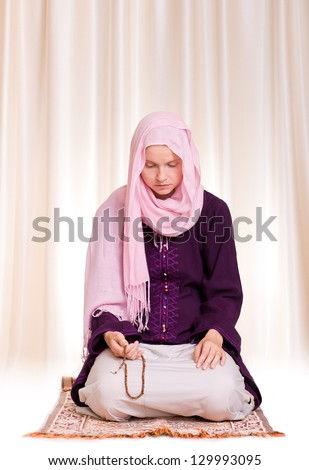 Young muslim woman praying with rosary - stock photo