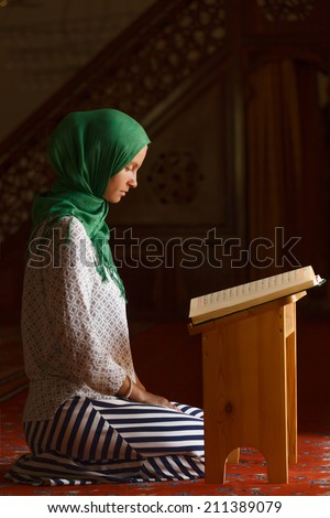 Young muslim woman reading Quran in turkish mosque  - stock photo