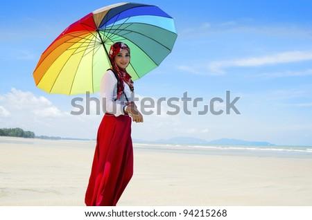 Young Muslim woman walking at beach. - stock photo