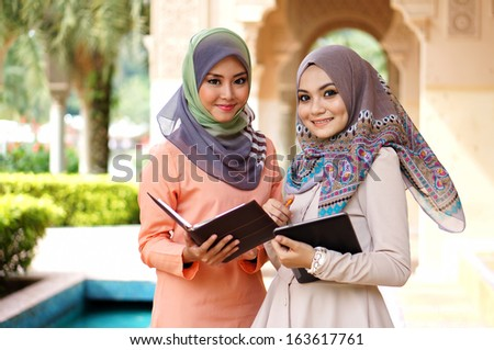 young muslimah woman discussing about their study in campus - stock photo
