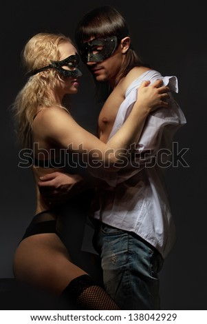 Young mysterious couple in a Venetian mask during sexual foreplay - stock photo