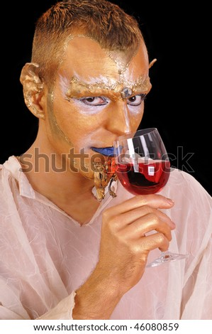 Young mystic artistic painted man with glass of beverage - stock photo