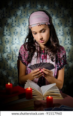 Young mystical woman playing fortune-teller - stock photo
