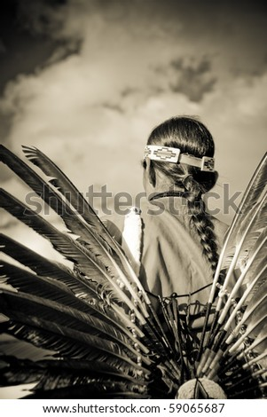 Young Naitive American man looking out over the plains, dressed traditionally - stock photo