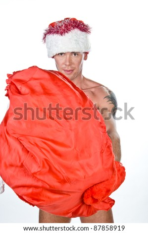 young naked guy in the cap of Santa Claus with a red bag in hand, isolated over white