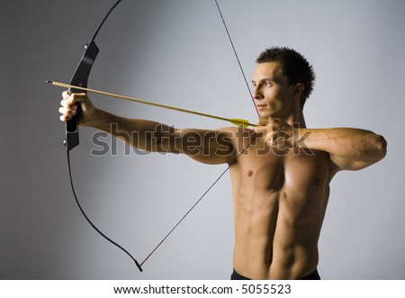 Young, naked man holding bow and shooting to target. Gray background - stock photo
