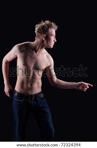 Young naked man in jeans posing on black