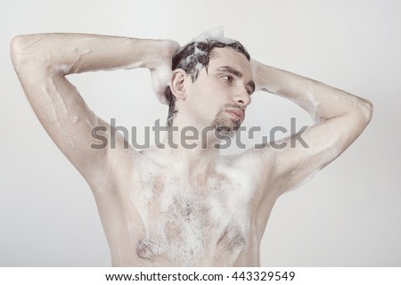Young naked man taking shower in the foam