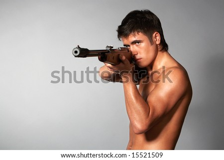 young naked man with rifle isolated on gray - stock photo