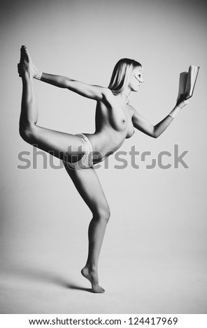 Young naked woman reading book. Black and white film style colors. - stock photo