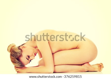 Young naked woman sitting curled up - stock photo