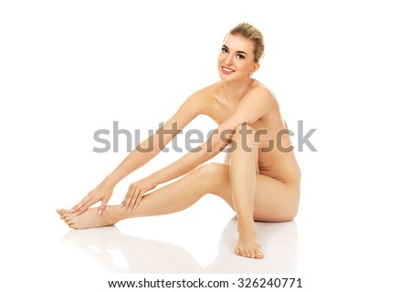 Young naked woman sitting on the floor.