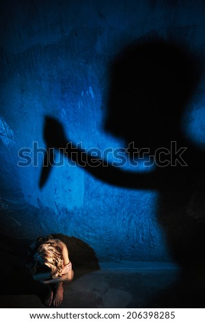 Young naked woman sitting on the floor. Hiding her face. Sexual parts are not visible. Shadow of man on the wall stubbing woman with knife. Rape, violence and murder concept. - stock photo