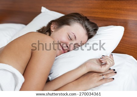 Young naked woman smiling in white bed in the morning