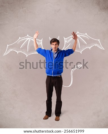 Young nasty man with devil horns and wings drawing - stock photo