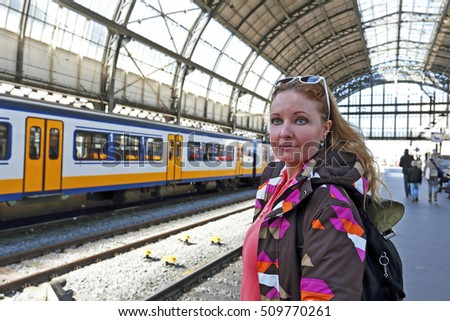 Young native dutch woman waiting for the train at the train station in Amsterdam Netherlands