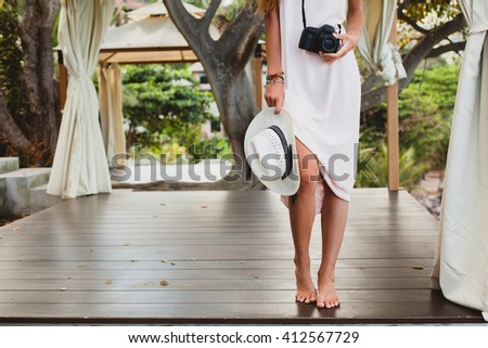 young natural beautiful woman in pale gown posing, tropical vacation, straw hat, holding digital camera, sensual, summer outfit, resort, boho vintage style, nature background, accessories, legs - stock photo