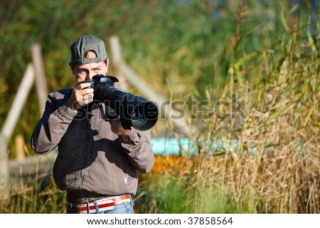 Young nature photographer with taking photos using telephoto lens - stock photo