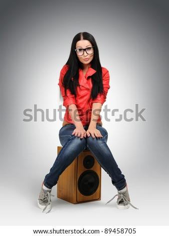 Young nerd fashion girl in large glasses with speaker - stock photo