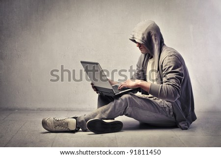 Young nerd using a laptop - stock photo
