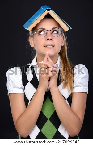 Young nerd woman crazy expression in glasses, holding book on head on black background - stock photo