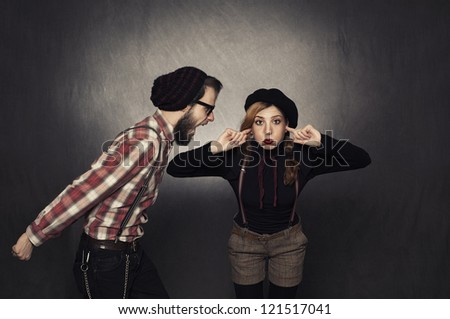 young nerdy girl not listening young nerdy man shouting on grunge background - stock photo