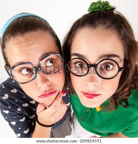 Young nerdy girls making faces and having fun. Studio shot.