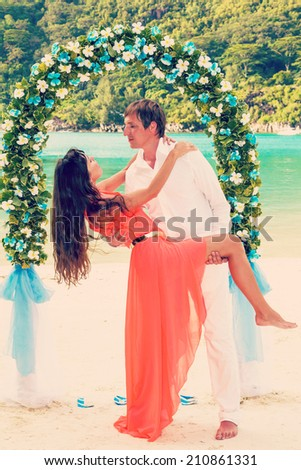 young newly married couple and wedding ceremony on the beach, the details of design, bouquet of frangipani, Seychelles - stock photo
