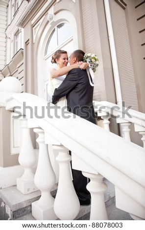 young newly married couple hugging on white stairs - stock photo