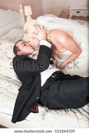 Young newly married couple kissing on bed - stock photo