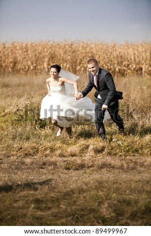 young newly married couple running in field - stock photo