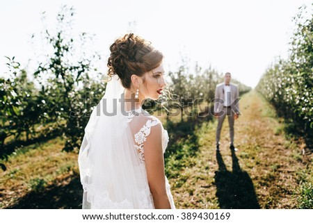 Young newly married couple walking in the young garden at the back light, chasing each other in the back light. bride has red lipstick and red bouquet. kisses, tenderly touches, caring, smiling - stock photo