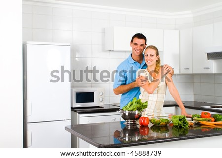 young newlywed couple in home kitchen - stock photo