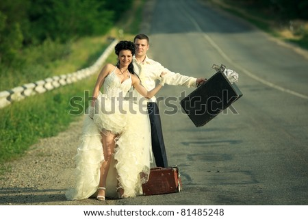 Young newlywed couple with suitcases of cash  hitchhiking on a road. - stock photo