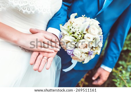 young newlyweds couple holding hands with rings and wedding bouquet - stock photo