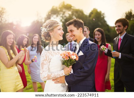 Young newlyweds enjoying romantic moment together at wedding reception outside, wedding guests in background blowing bubbles - stock photo