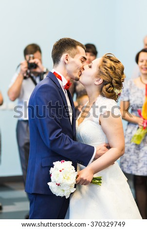 Young newlyweds kissing and enjoying romantic moment together at wedding reception outside, wedding guests in background - stock photo