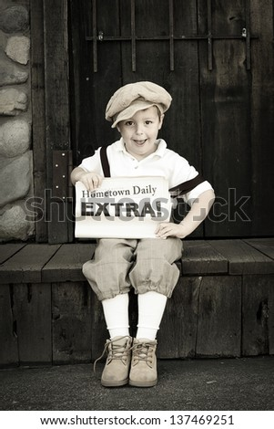 Young newsboy holding his paper with space for a headline - stock photo