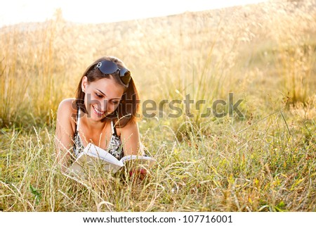 Young nice attentive woman lies on grass and reads book at summer field - stock photo