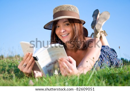 Young nice attentive woman lies on green grass and reads book - stock photo