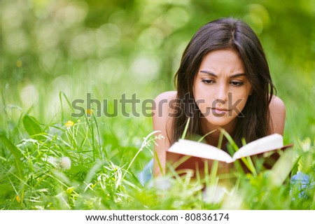 Young nice attentive woman lies on green grass and reads book against city park. - stock photo