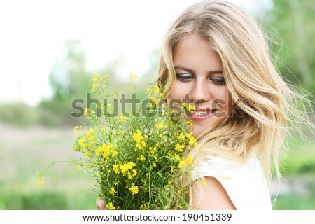 Young nice blond woman smiling looking away and holding bouquet yellow wild flowers spring closeup - stock photo