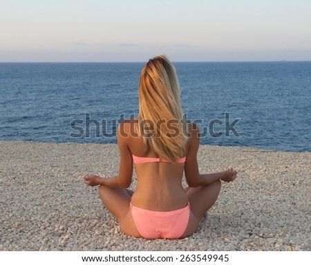 Young nice body european woman meditation on a sand with the view to the sea, woman in the beach,yoga with the view to the sea, unknown girl in the beach, summer holidays - stock photo