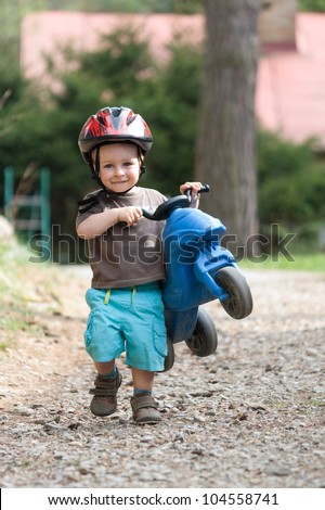 Young nice boy with safety helmet and children's bike - stock photo