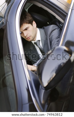 young nice businessman at the wheel in the car - stock photo
