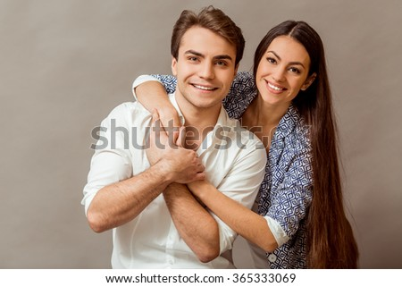 Young nice couple posing in the studio, express emotions and gestures, smiling, on a gray background - stock photo