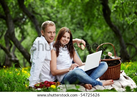 Young nice couple with the laptop in forest - stock photo