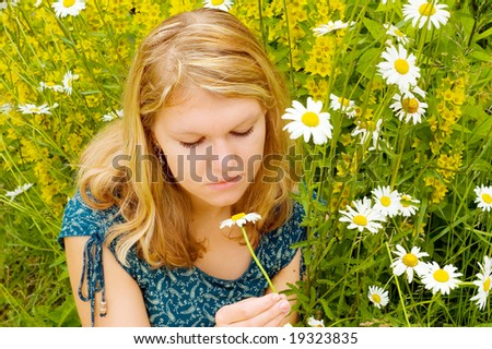 Young nice girl with close eyes lying in grass and relaxing with chamomile - stock photo
