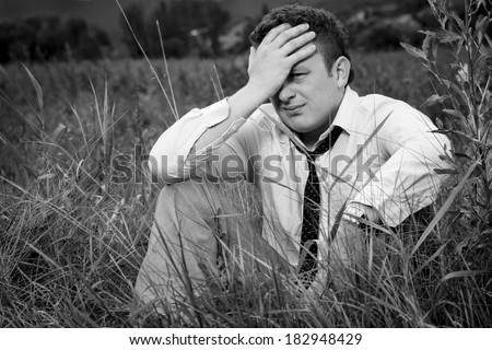 Young, nice man sitting in the meadow, her head propped on her hand. He can not even believe what happened. He's in  hopeless situation.  - stock photo